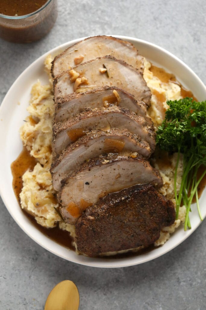 slow cooker pork loin on a bed of mashed potatoes covered in delicious homemade gravy
