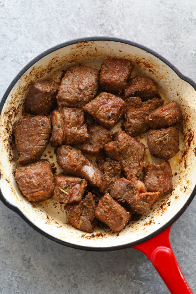 beef stew meat being browned in in a skillet