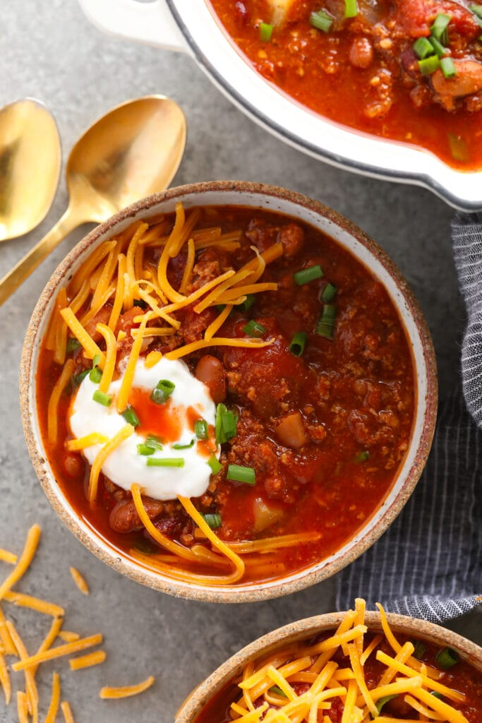 turkey chili topped with sour cream and shredded cheese in a bowl