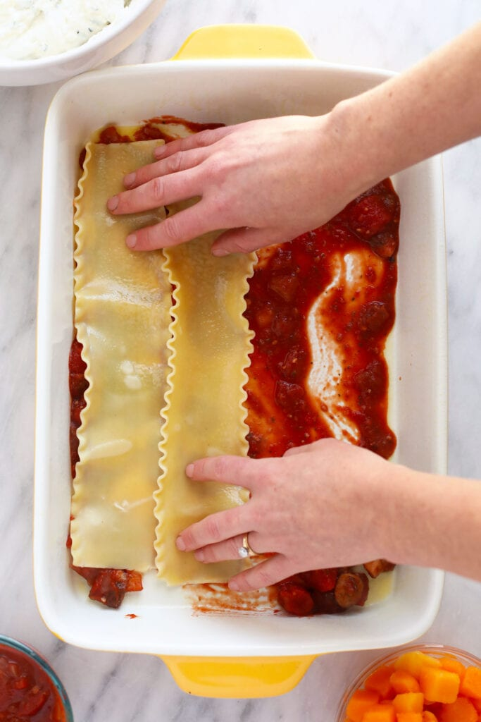 Hands placing lasagna noodles in a 9x13 casserole dish.