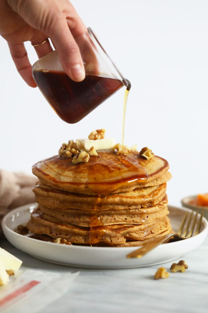Pouring maple syrup over sweet potato pancakes.