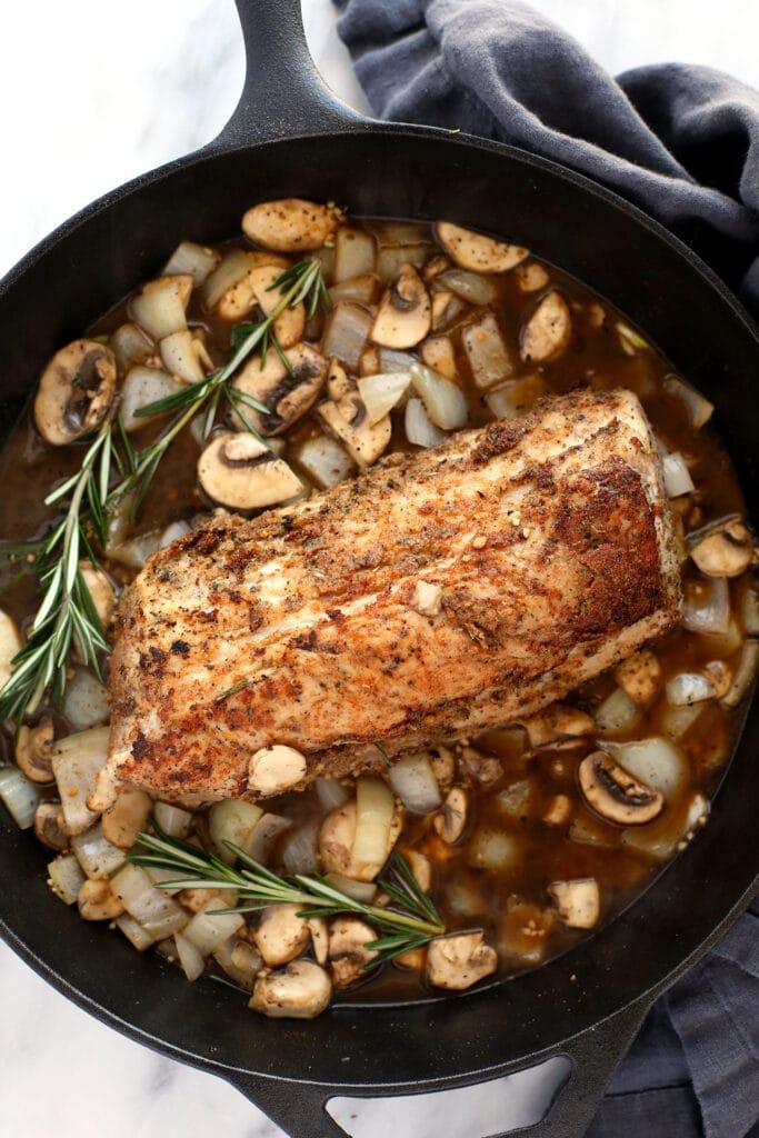 pork tenderloin in gravy on cast iron pan