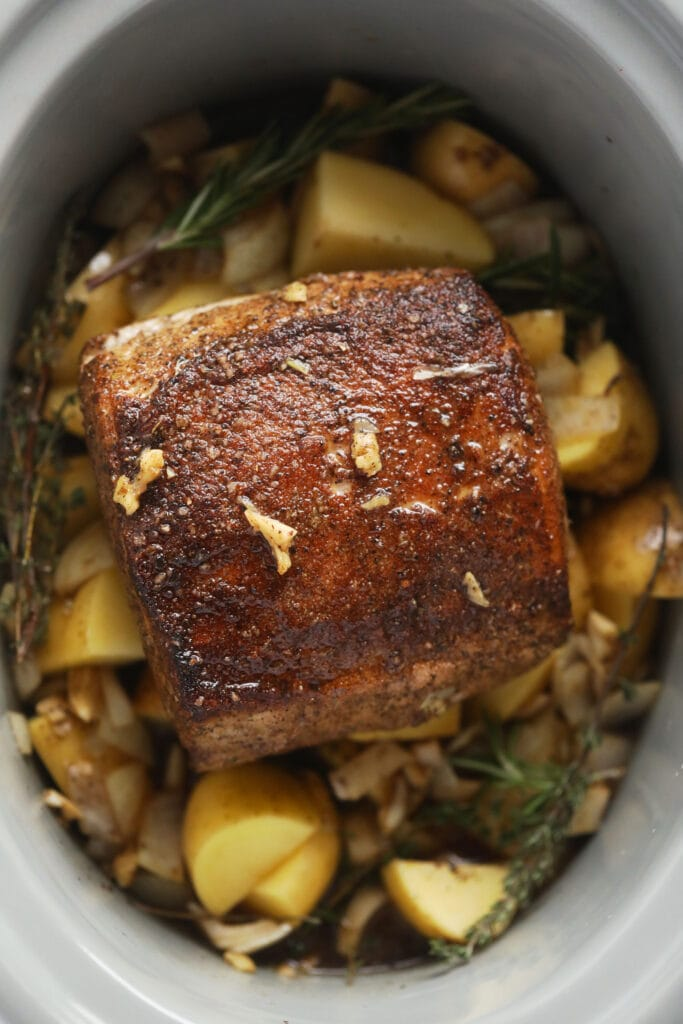slow cooker pork loin roast on a bed of potatoes and herbs in the slow cooker