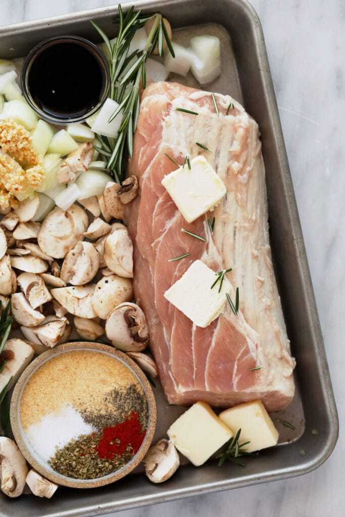 raw pork with mushrooms and butter on sheet pan