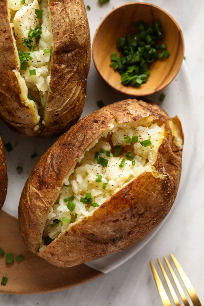 Baked potatoes on a plate with butter, salt, pepper, and chives.