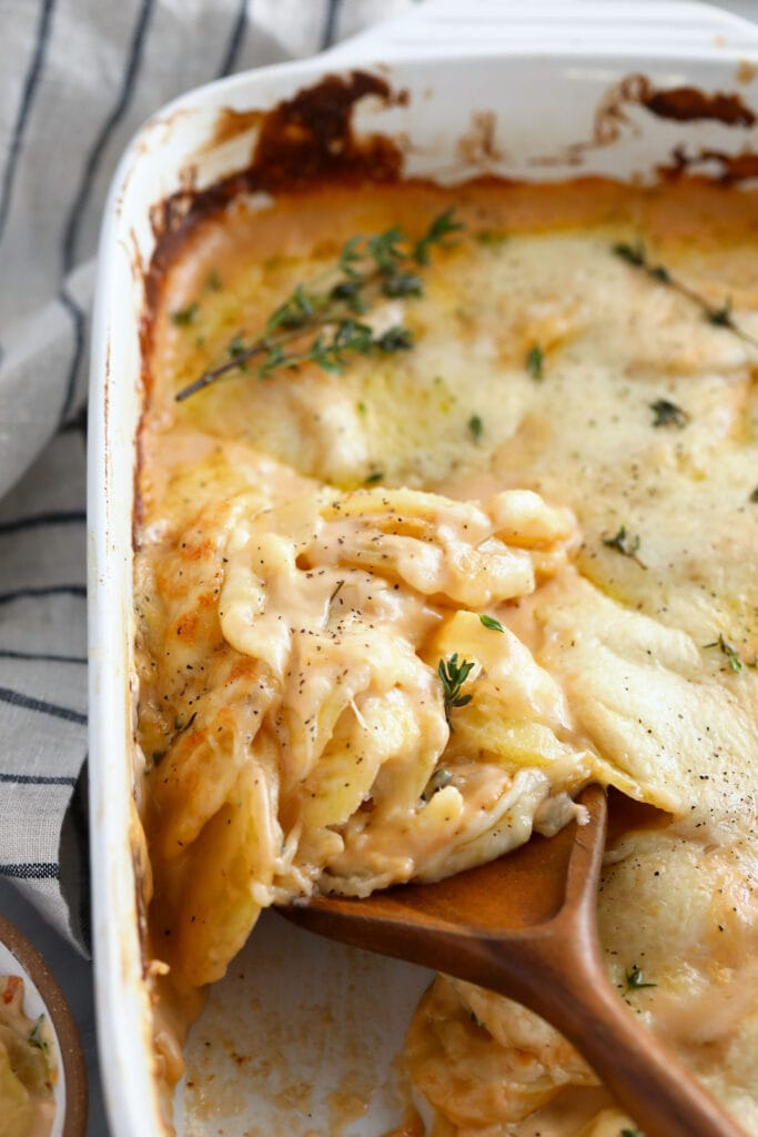 Cheesy scalloped potatoes in a casserole dish.