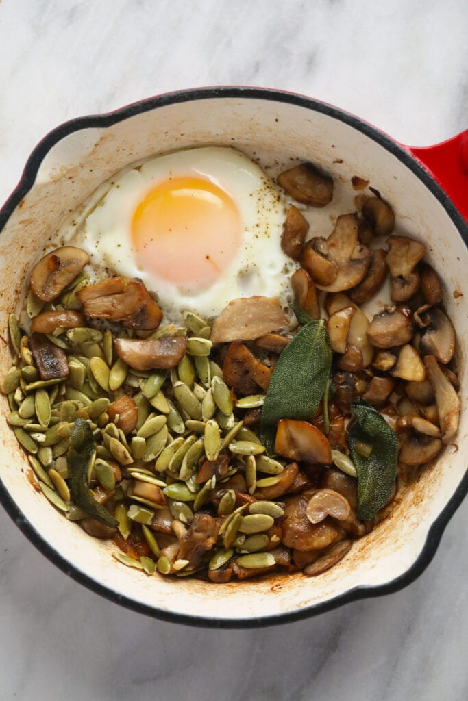 Savory oatmeal in a small pot with savory toppings, including an egg.