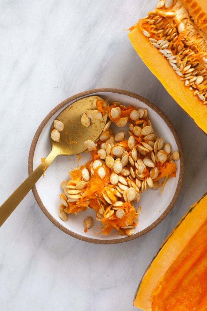 delicata squash seeds being scooped out with a spoon