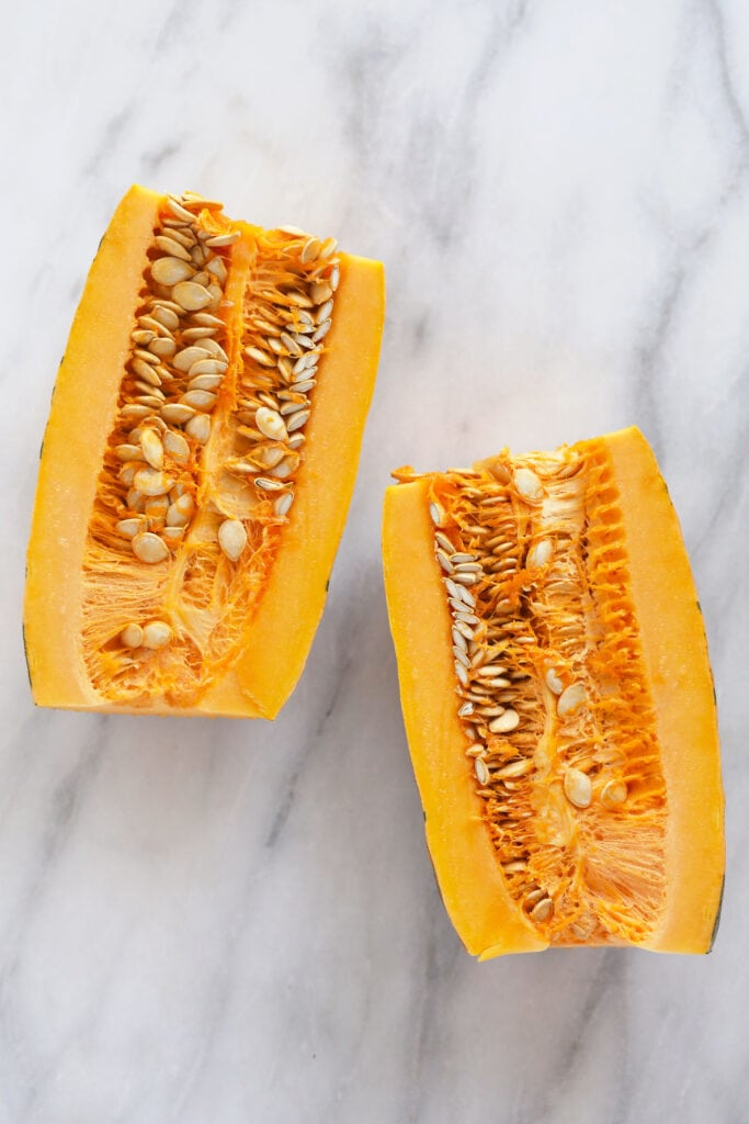 delicata squash cut in half with the seeds ready to be removed