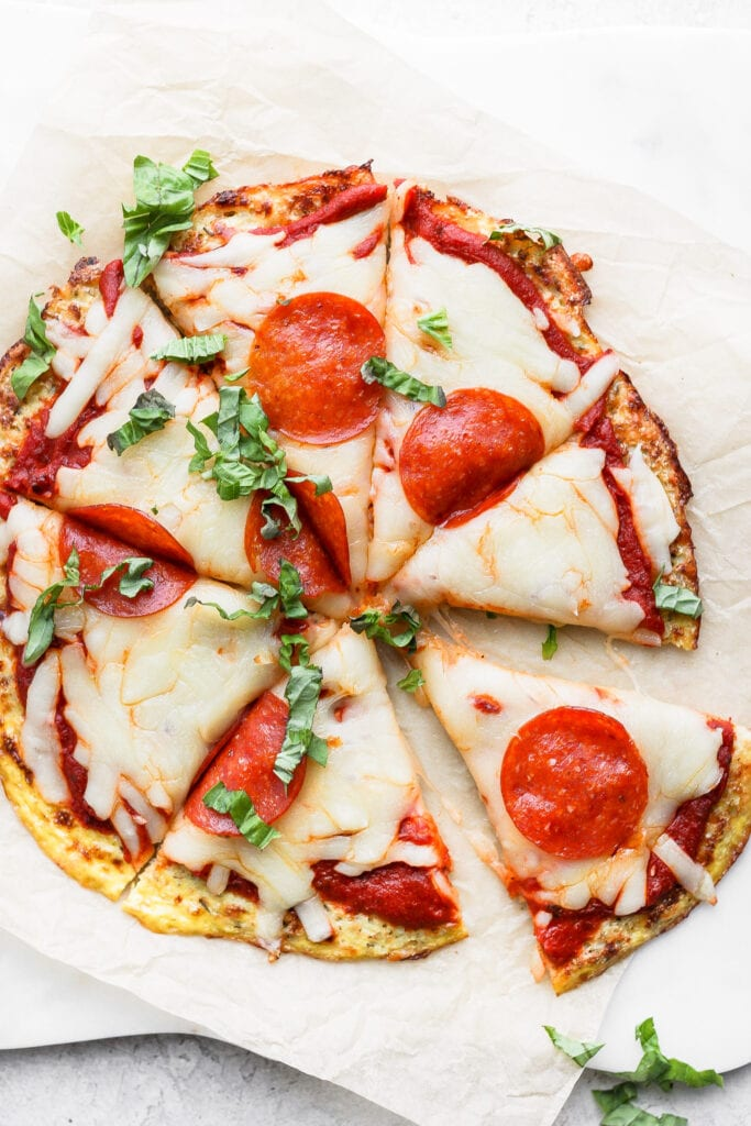 Cauliflower pizza crust topped with cheese, pepperoni, and fresh basil.