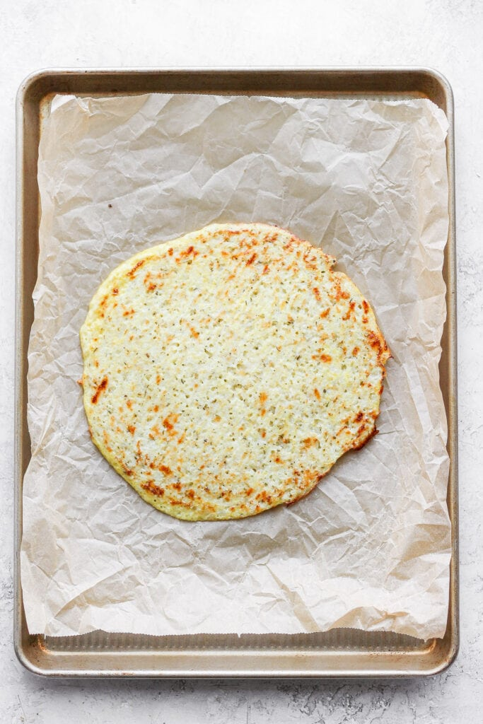 Golden cauliflower pizza crust on parchment paper.