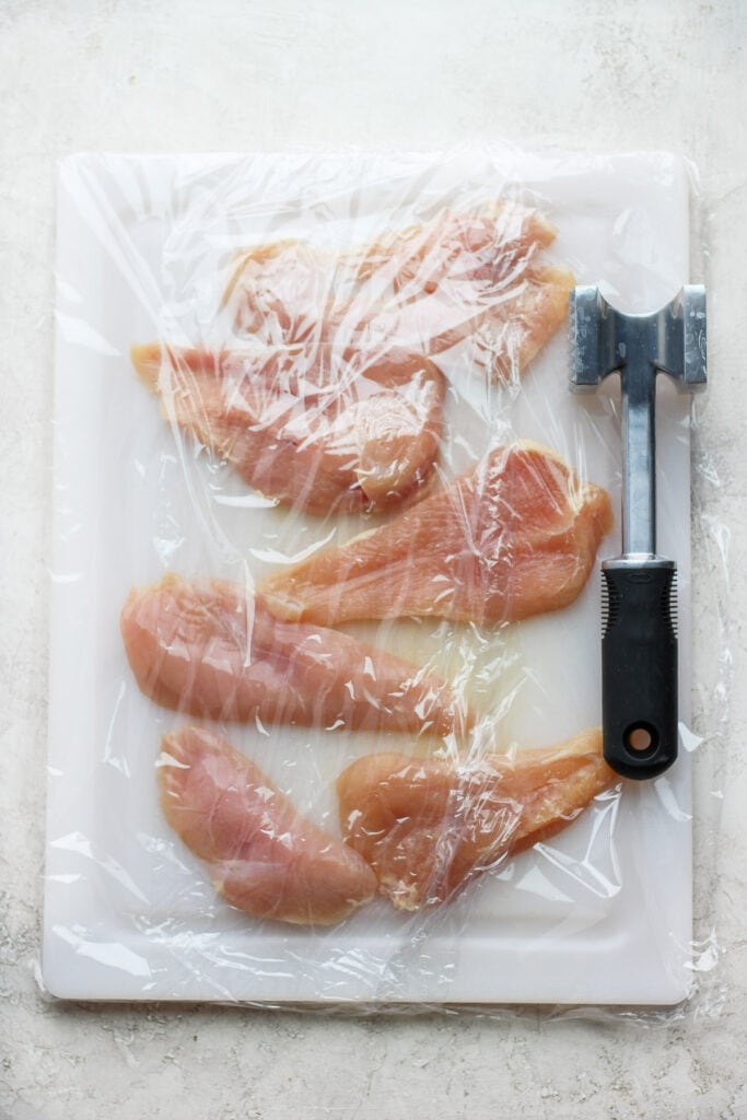 raw chicken breasts ready to be pounded to equal thickness