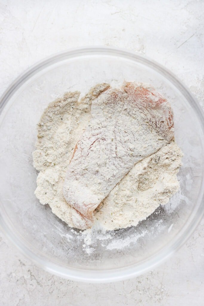 raw chicken breast being dredged in seasonings and flour