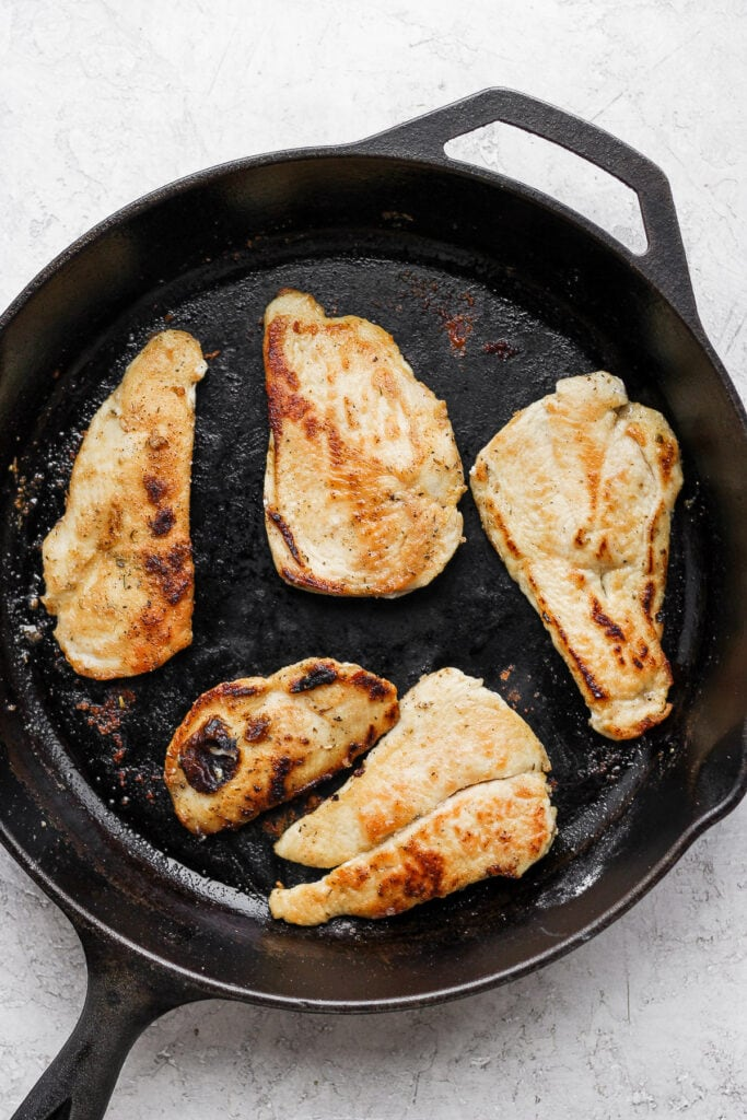 chicken breasts being seared in a cast iron skillet for chicken marsala