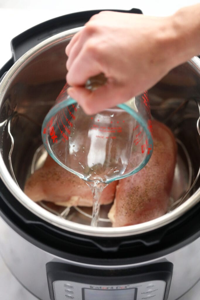 water being poured in the instant pot for instant pot shredded chicken