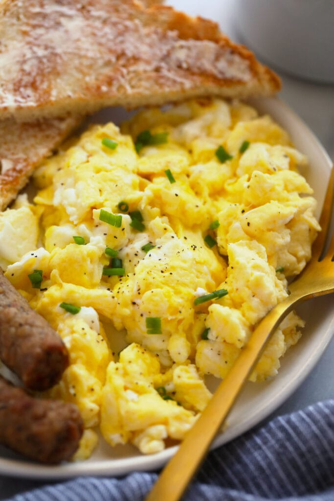 perfect scrambled eggs on a plate with toast and sausage links, ready to be served