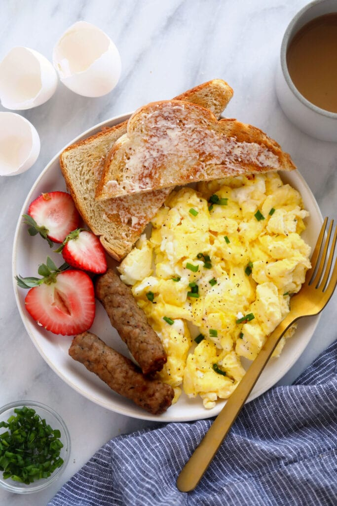 scrambled eggs on a plate with fresh fruit and toast