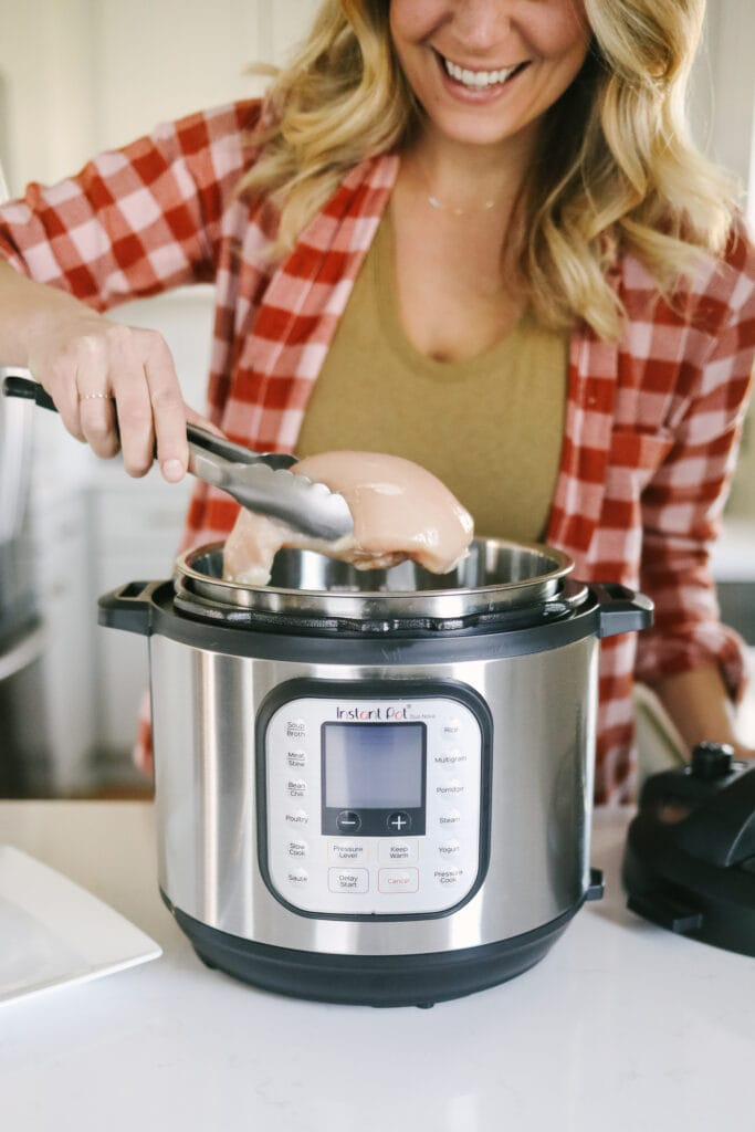 A woman putting chicken breast in an Instant Pot.