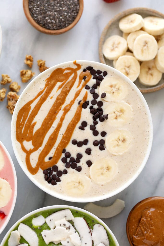 peanut butter banana smoothie bowl with mini chocolate chips, banana, and peanut butter