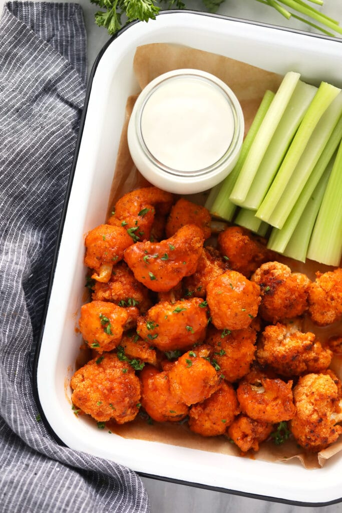 air fryer buffalo cauliflower in container with blue cheese dip and celery