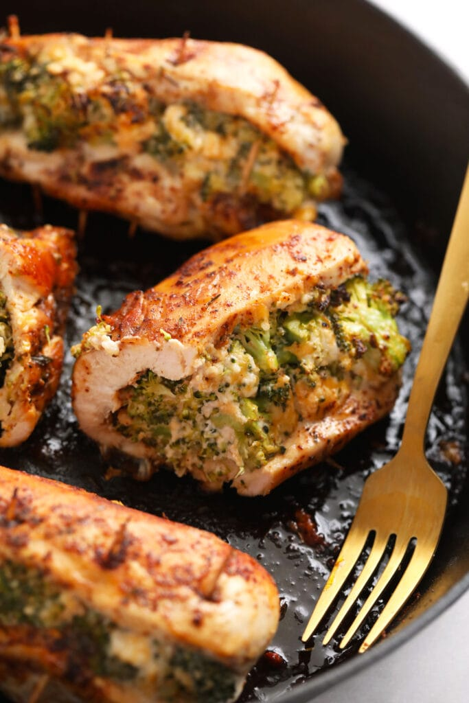 broccoli and cheese stuffed chicken breast in a cast iron skillet