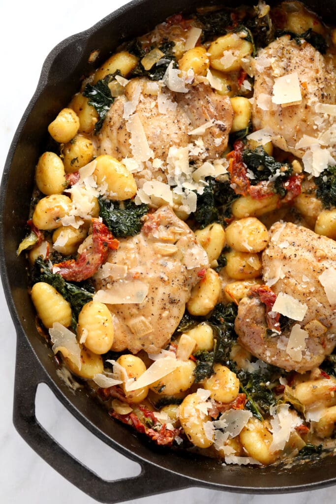 creamy tuscan chicken and gnocchi in a cast iron skillet ready to be served