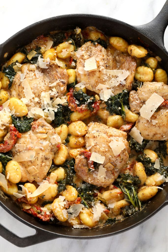 creamy tuscan chicken and gnocchi in a cast iron skillet topped with parmesan