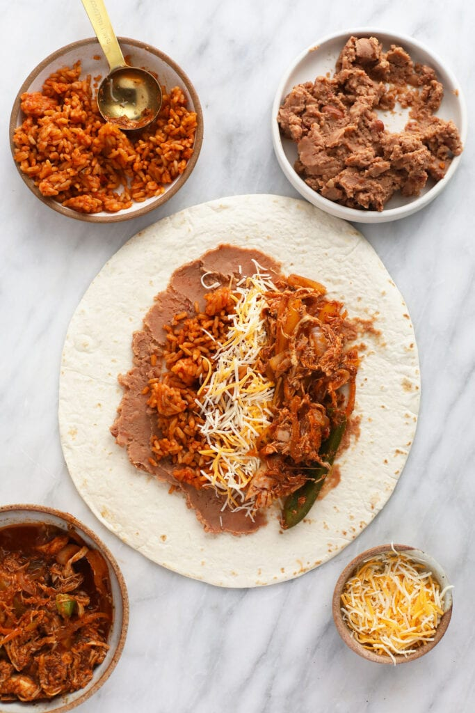 shredded chicken burrito ingredients being assembled onto a flour tortilla