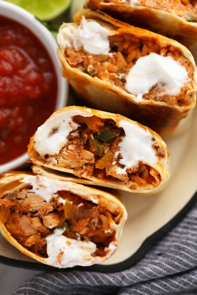 shredded chicken burritos cut in half and topped with sour cream