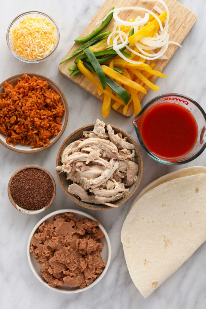 ingredients for shredded chicken burritos, ready to be assembled