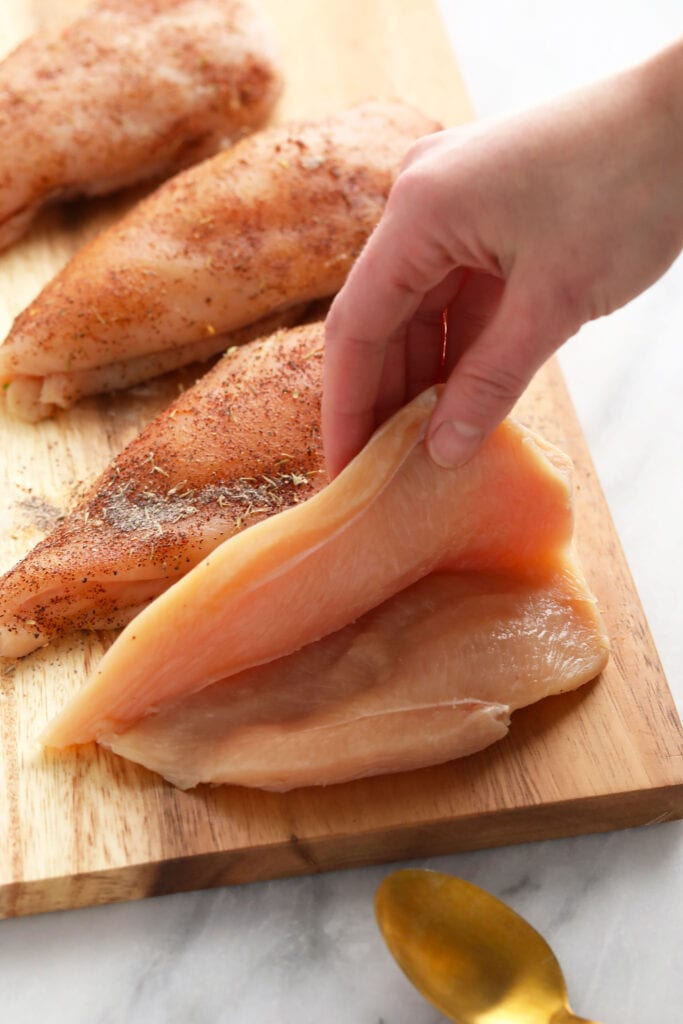 raw chicken breast cut open, ready to be stuffed with broccoli and cheese filling