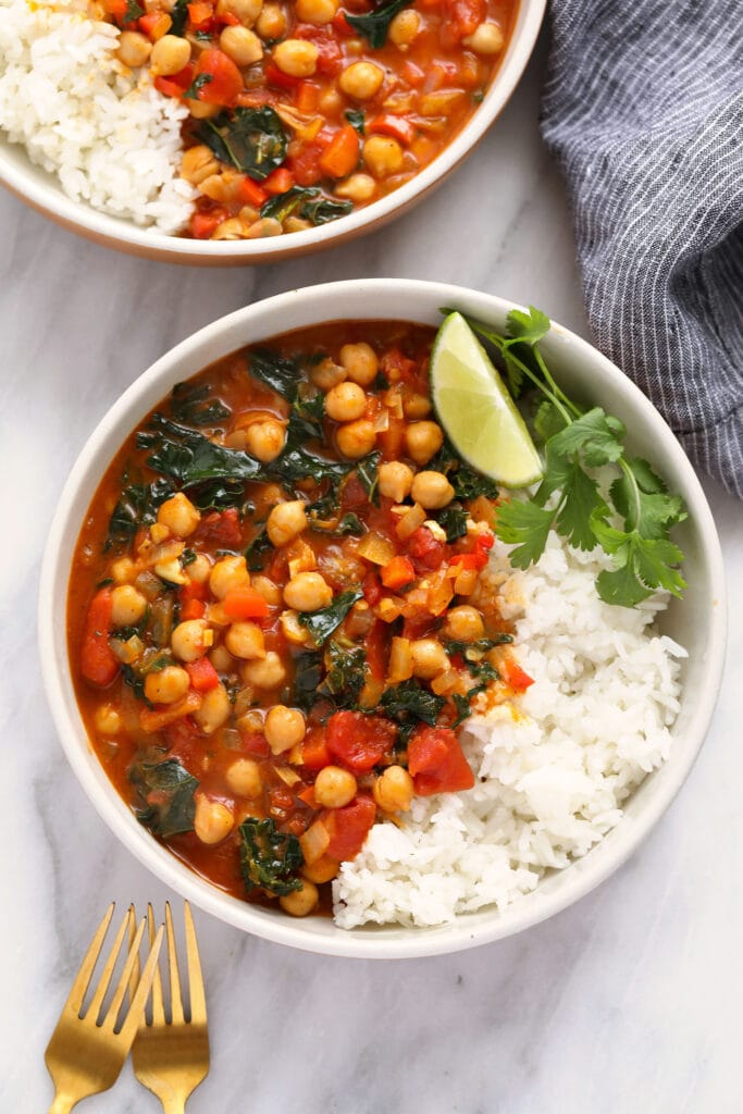 chickpea curry in a bowl with a side of rice