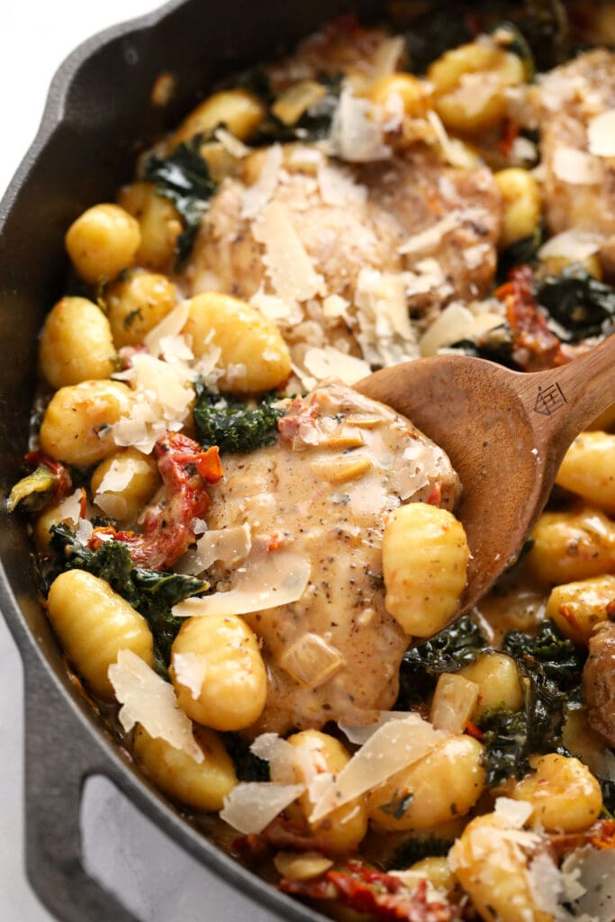 creamy tuscan chicken and gnocchi in a cast iron skillet