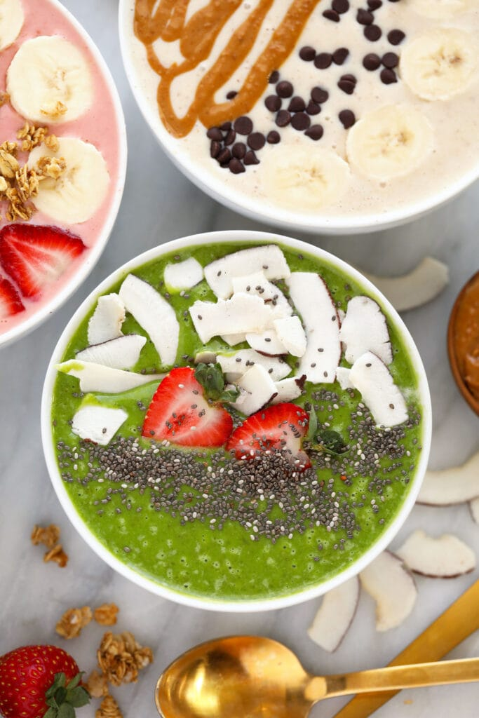green smoothie bowl with strawberries, coconut, and chia seeds