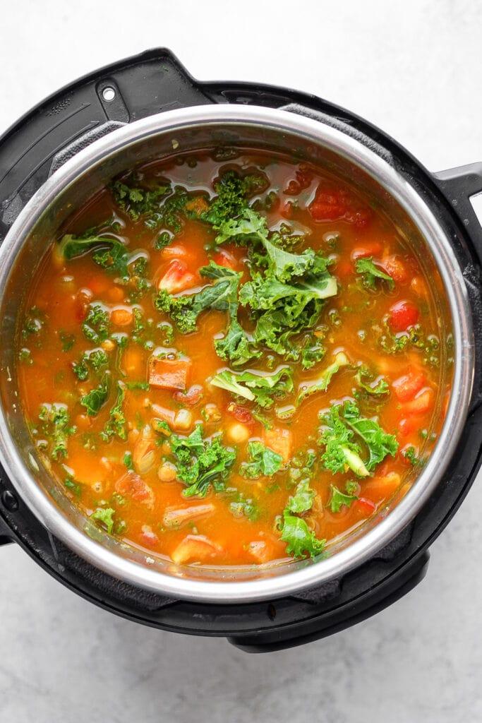 Instant Pot lentil soup with fresh kale on top.