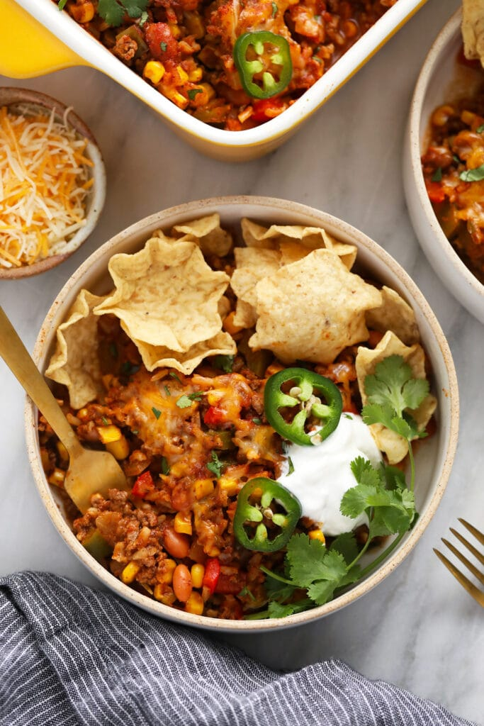 Mexican casserole in a bowl with tortilla chips.