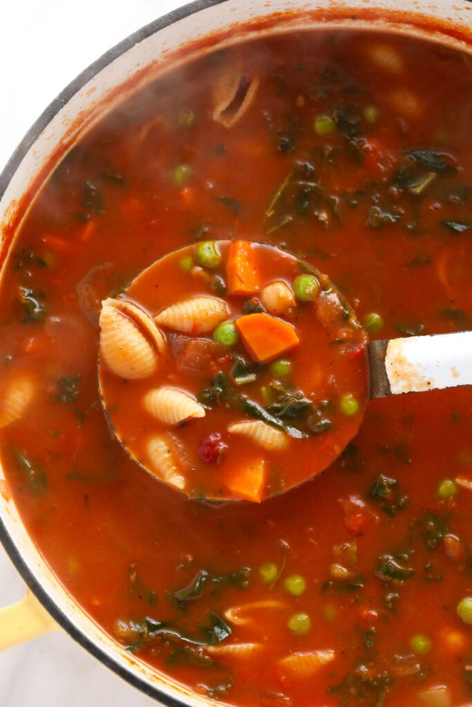 A ladle full of minestrone soup.