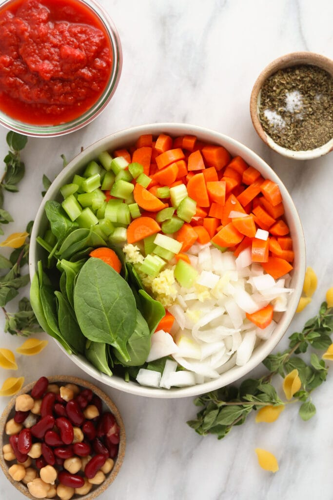 A bowl of carrots, celery, onion, garlic, and spinach.