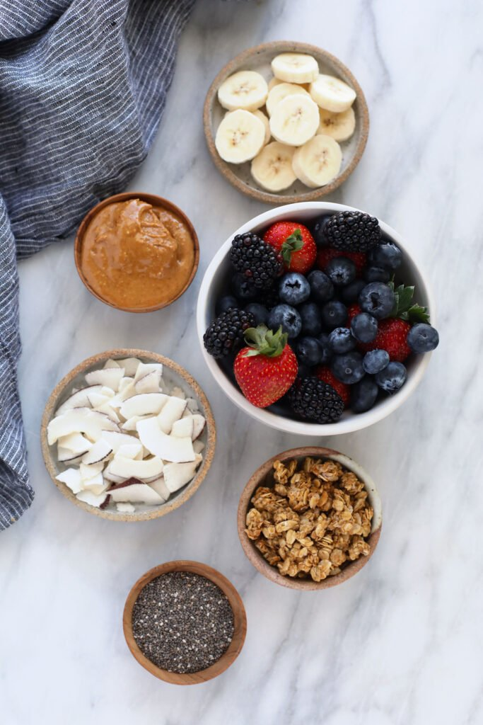 berries, peanut butter, coconut, granola, chia seeds, and banana slices