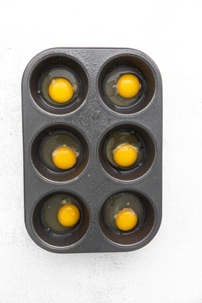 raw eggs in a muffin tin