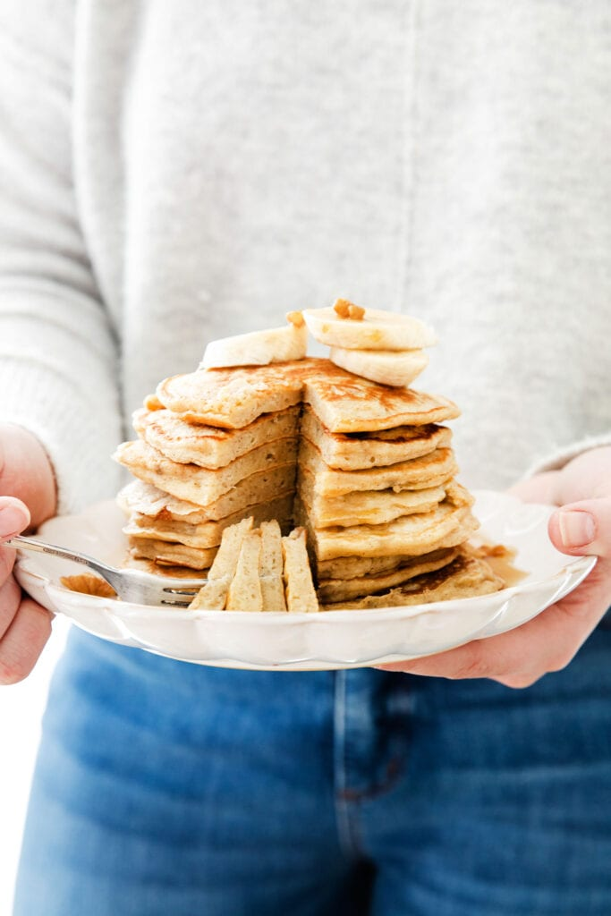 holding a plate of easy banana pancakes