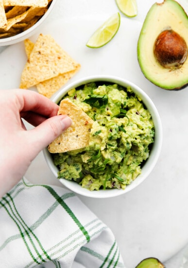 A tortilla chip scooping up guacamole.