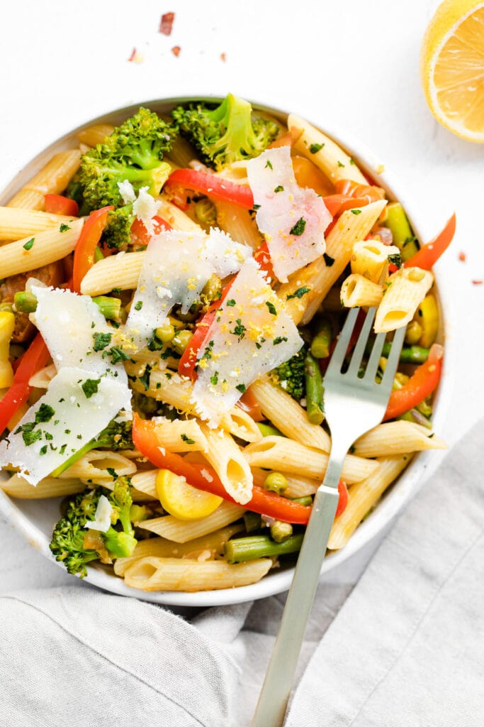 pasta primavera in a bowl topped with parmesan cheese and fresh basil