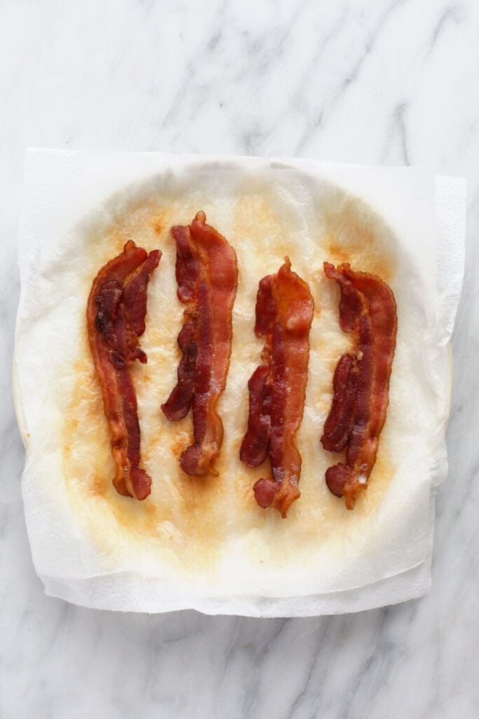 Cooked bacon on a plate that is covered in paper towel.