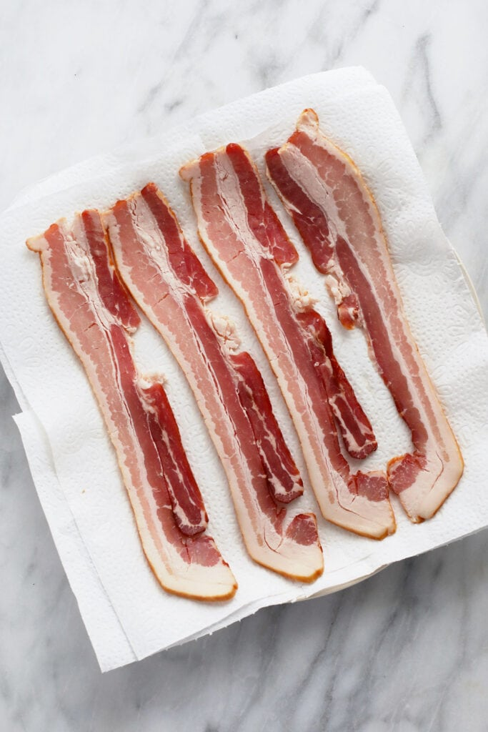 Raw bacon on a plate on top of paper towel.