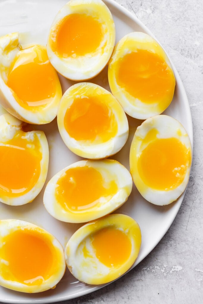 Soft boiled ramen eggs on a plate.