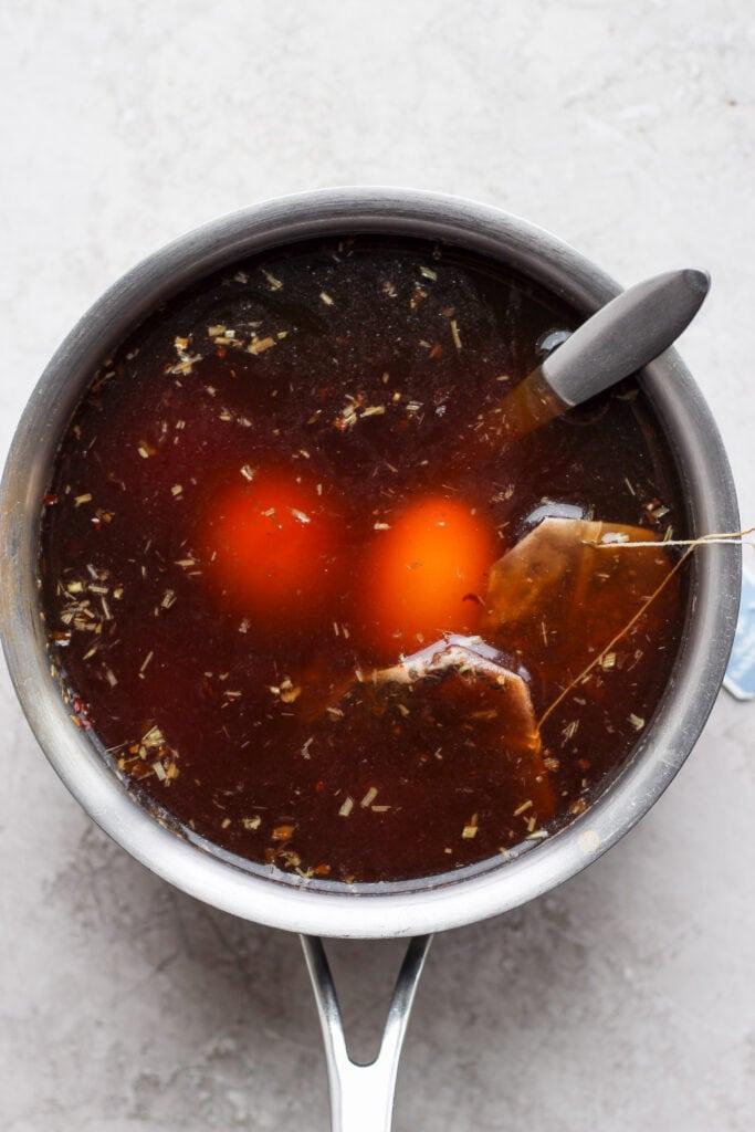 Marinating ramen eggs in a black tea mixture.