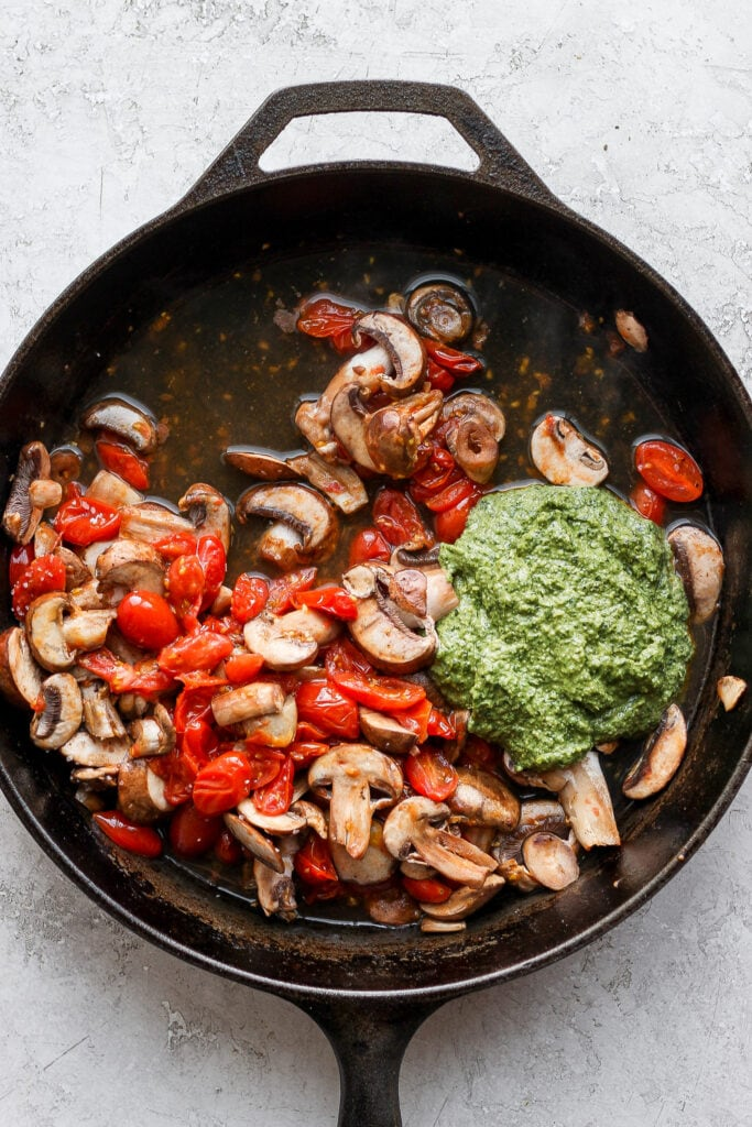 Pesto and vegetables in a cast iron skillet.
