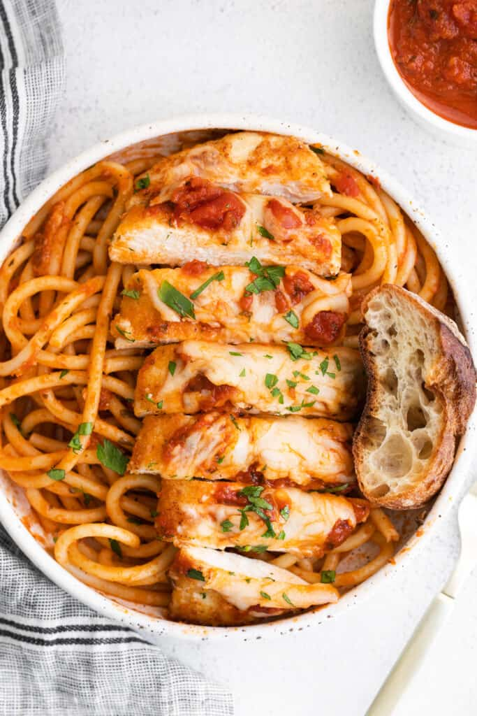 sliced chicken parmesan on noodles