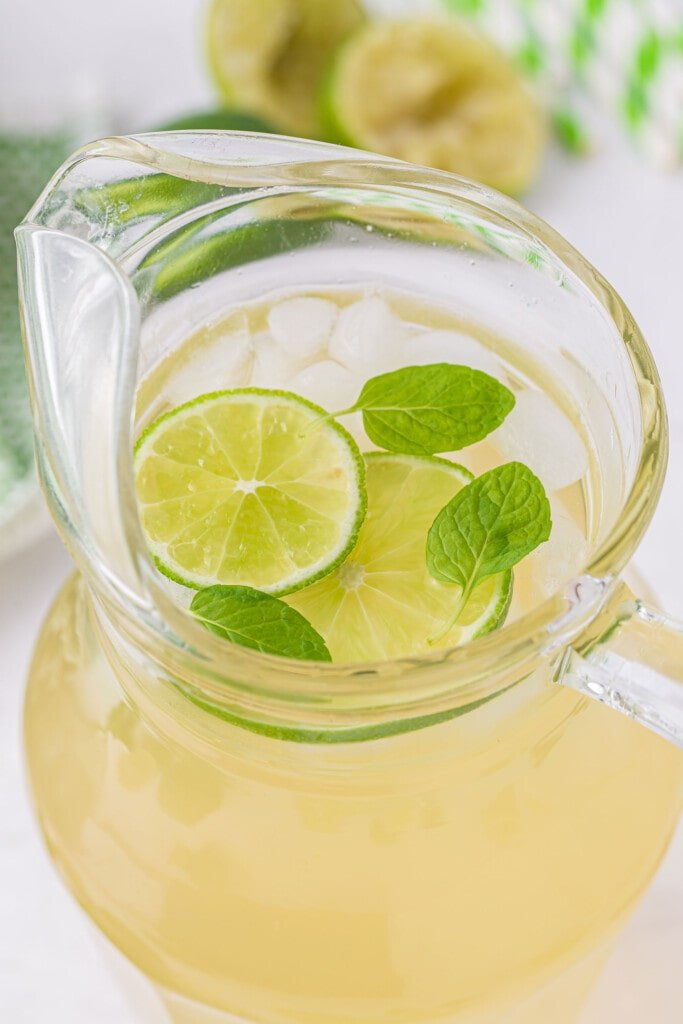 limeade in a pitcher with ice and fresh lime slices looking delicious